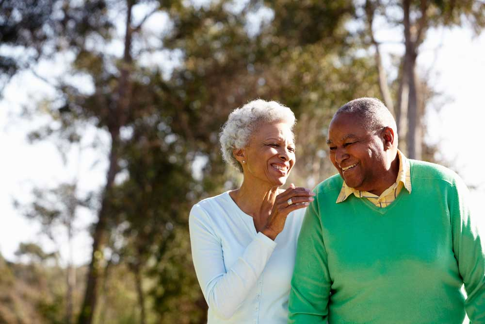 An elderly couple enjoys a walk in the park after learning more about Medicare Supplement (Medigap) insurance